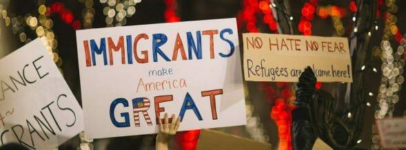 """gente sosteniendo carteles que dicen """"los inmigrantes hacen a america grande"""""""