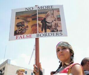 """Mujer protestando """"no más falsas fronteras"""" a favor de los migrantes y dreamers y contra las deportaciones"""
