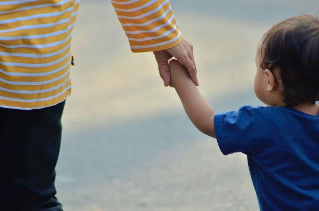 Niño tomando de la mano a un adulto - Familias migrantes separadas