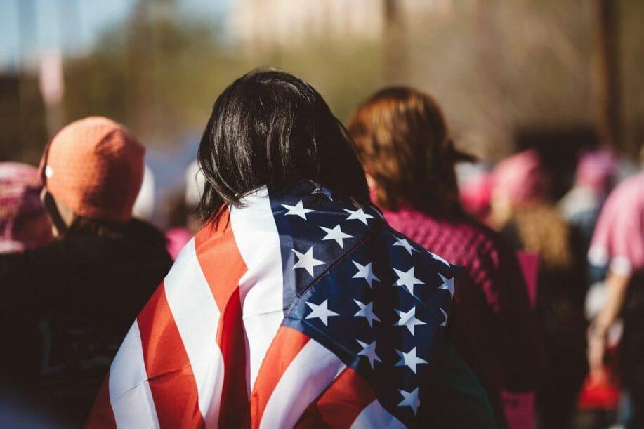 mujer con bandera de estados unidos en su espalda - este artículo habla acerca de la ley de migración y la reforma migratoria integral