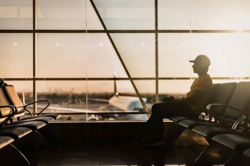 hombre espera sentado en un aeropuerto. Hay importantes demoras en los tramites de visados en estados unidos