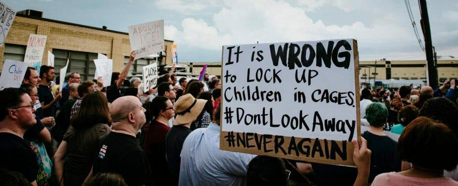 La imagen muestra una protesta donde las personas sujetan carteles que piden acciones para proteger a las familias migrantes en la frontera