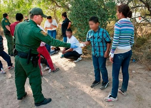 Nota informando sobre la decisión de la Corte Suprema respecto al programa Remain in Mexico. La foto es de migrantes junto a un agente de la Patrulla Fronteriza.