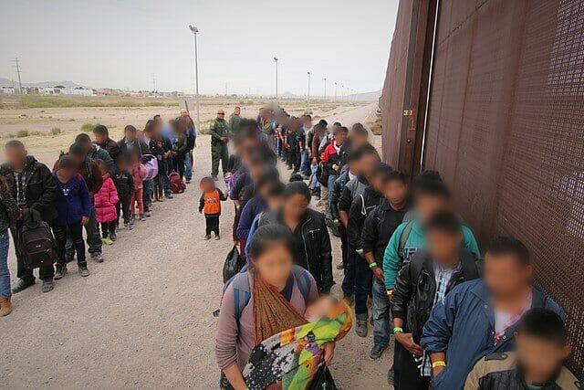 Nota informando sobre la decisión de la Corte Suprema respecto al programa Remain in Mexico. La foto es de migrantes esperando junto al muro fronterizo entre México y Estados Unidos.