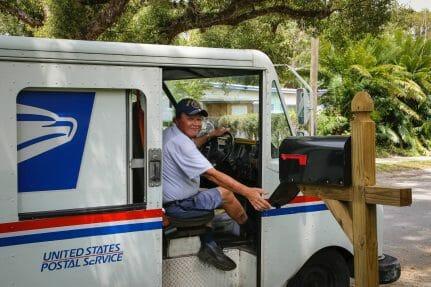 Nota explicativa sobre cómo puedo saber cuando me llega mi green card. La imagen es de un trabajador del Servicio Postal de los Estados Unidos.